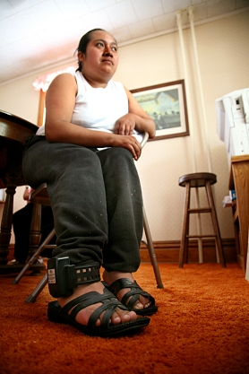 A Hispanic woman sits in a folding chair; an electronic monitoring device is locked to her ankle.