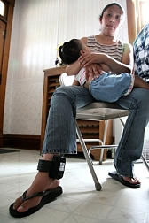 A young Hispanic woman holding her daughter; locked onto her ankle is an electronic monitoring device.